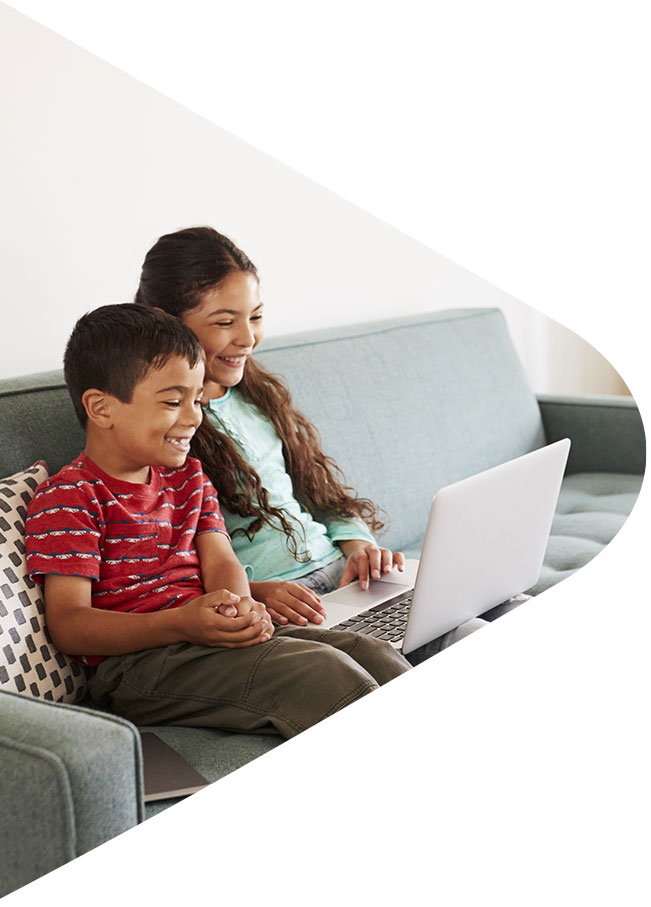 Kids on the couch watching video on laptop